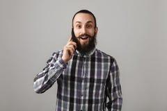 有胡子的英俊的人由在蓝色被摆正的衬衣o的电话谈话 库存图片