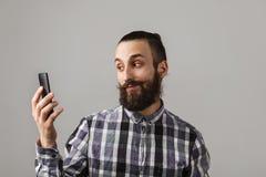 有胡子的英俊的人由在蓝色被摆正的s的电话采取selfie 图库摄影