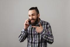 有胡子的英俊的哀伤的人由在蓝色被摆正的shi的电话谈话 库存照片