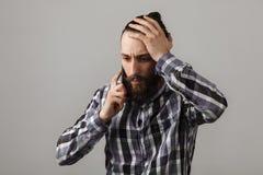 有胡子的英俊的哀伤的人由在蓝色被摆正的shi的电话谈话 免版税库存图片