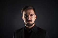 有胡子的英俊的残酷人在黑暗的背景 免版税库存图片