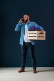 年轻有胡子的英俊的男性行家,打扮在牛仔布衬衣和白色T恤杉,站立户内拿着有花的木箱 图库摄影