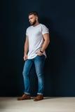年轻有胡子的英俊的行家人,打扮在有短的袖子和牛仔裤的白色T恤杉,站立户内 库存照片