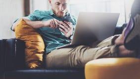 有胡子的行家运作的膝上型计算机现代设计内部演播室顶楼 人工作葡萄酒沙发,使用当代笔记本 库存照片