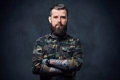 有胡子的被刺字的行家男性画象在一件军用夹克穿戴了 免版税库存照片