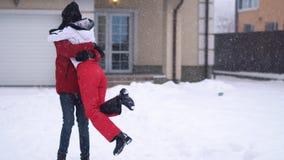 有胡子的转动在他的女朋友附近的人佩带的冬天夹克,笑 愉快的夫妇获得一个乐趣在冬天 股票视频