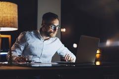 有胡子的运转在现代顶楼办公室的商人佩带的白色衬衣在晚上 使用当代笔记本发短信的人 图库摄影