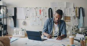 有胡子的速写使用膝上型计算机的人设计师画的衣裳在现代演播室 股票视频
