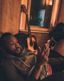 有胡子的非洲年轻黑人使用智能手机放下在教练和吉他的 库存照片