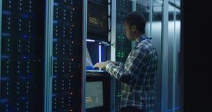 有胡子的非裔美国人IT专家在数据中心的设置服务器 库存照片