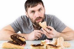 有胡子的食人的杯形蛋糕高兴地在饮食以后的 有害,但是可口食物 免版税库存照片