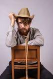 有胡子的年轻人坐一把棕色椅子 免版税库存图片