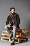 有胡子的年轻时髦的人,穿夹克坐板台 免版税库存图片