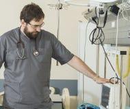 有胡子的医生佩带的玻璃和一件灰色长袍与医院设备一起使用 免版税库存图片