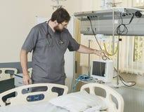 有胡子的医生佩带的玻璃和一件灰色长袍与医院设备一起使用 库存照片