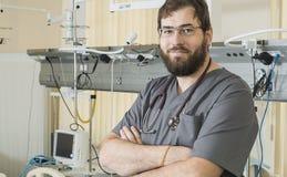 有胡子的医生佩带的玻璃和一件灰色长袍与医院设备一起使用 库存图片