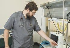 有胡子的医生佩带的玻璃和一件灰色长袍与医院设备一起使用 免版税图库摄影