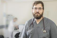 有胡子的医生佩带的玻璃和一件灰色长袍立场在前景对弄脏助理的背景 免版税库存图片