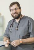 有胡子的医生佩带的玻璃和一件灰色长袍 免版税库存图片