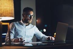 有胡子的年轻运转在现代顶楼办公室的商人佩带的白色衬衣在晚上 使用当代笔记本的人 免版税库存图片