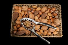 有胡桃钳的混杂的坚果在柳条筐 免版税库存照片