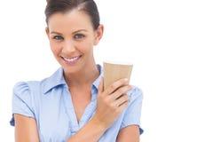 有胳膊横渡的和咖啡杯的微笑的女实业家 免版税库存图片