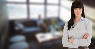 有胳膊横渡的身分的女实业家在办公室 免版税库存图片
