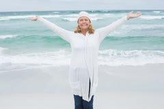 有胳膊的偶然资深妇女伸出在海滩 库存图片
