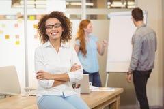 有胳膊的女实业家在背景中横渡了与同事 免版税图库摄影