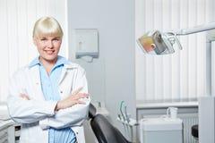 有胳膊的女性牙医在口腔实习横渡了 免版税库存照片