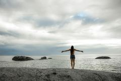有胳膊的妇女在岩石传播了在Bakovern海滩,开普敦的日落 库存图片