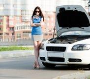 有胳膊的妇女在残破的汽车附近横渡了 免版税库存图片
