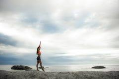 有胳膊的妇女悬而未决在岩石在Bakovern海滩,开普敦的日落 库存照片