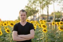 有胳膊的年轻英俊的人横渡了反对开花的s的领域 免版税库存图片