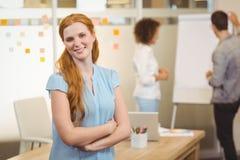 有胳膊的微笑的女实业家在背景中横渡了与同事 免版税库存照片