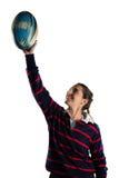 有胳膊的愉快的女运动员提高了拿着橄榄球球 免版税库存图片