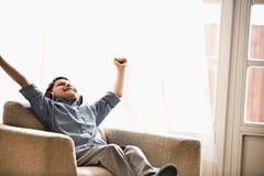 有胳膊的愉快的男孩提高了享受音乐,当在家时放松在扶手椅子 免版税库存照片