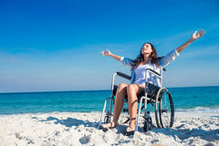 有胳膊的残疾妇女伸出在海滩 免版税库存照片