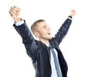 有在成功举的胳膊的激动的英俊的商人 免版税图库摄影