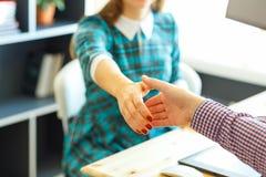 有胳膊的现代女商人延伸到握手 库存图片