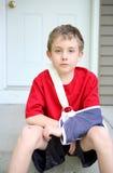 有胳膊的男孩在从断肱骨的吊索 库存图片