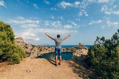 有胳膊的自由的愉快的男性旅客被举对在休息的天空是在山顶部 免版税库存图片