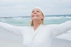 有胳膊的资深妇女被伸出在海滩 免版税图库摄影