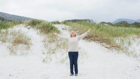 有胳膊的资深妇女被伸出在海滩 免版税库存照片