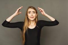 有胳膊的震惊女孩在充分的怀疑的空气 免版税库存照片