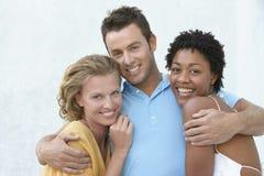 有胳膊的年轻人环绕两个女性朋友 免版税库存照片