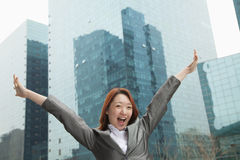 有胳膊的年轻快乐的女实业家在摩天大楼,北京中伸出 免版税库存照片