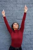 有胳膊被举的和手指的指向愉快的年轻的黑人妇女  库存照片