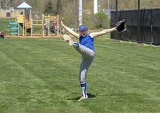 有胳膊被伸出的和腿的热心女孩垒球运动员踢了高 库存图片