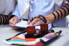 有胳膊tefillin的宗教正统犹太人在他的左手祈祷 图库摄影